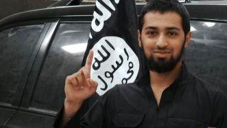 Talha Asmal posing with an ISIS flag